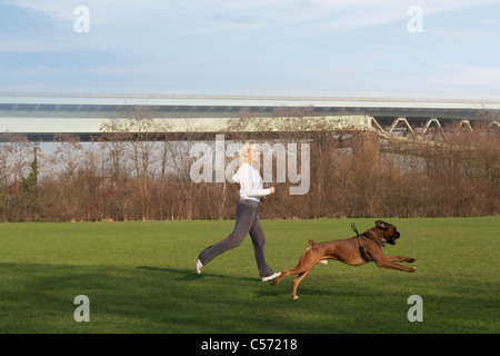 Woman running with dog in field - Stock Photo
