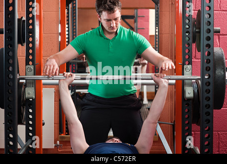 Men lifting weights in gym - Stock Photo