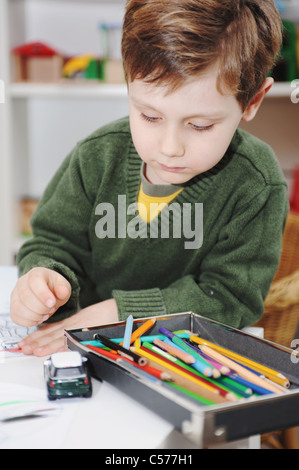 Boy drawing with colored pencils - Stock Photo