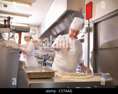 Chef making bread in restaurant kitchen - Stock Photo