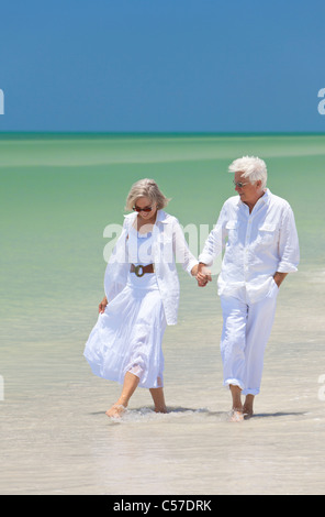 Happy senior man and woman couple walking, smiling and holding hands on a deserted tropical beach with bright clear - Stock Photo
