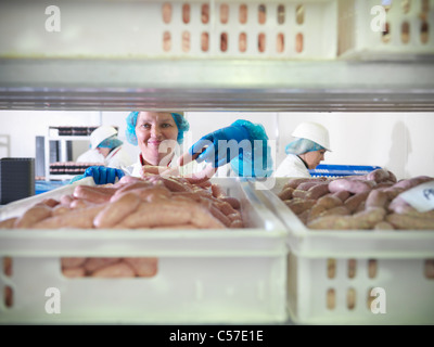 Worker inspecting sausages in factory - Stockfoto