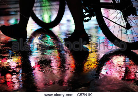 Wet city street lit by neon lights - Stock Photo