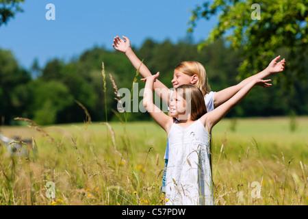 Happy children in a meadow in summer - Stock Photo