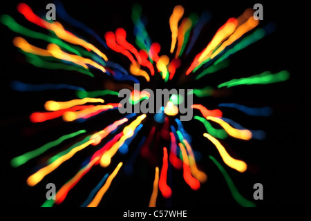 Multicolored streaks of light against a black background - Stock Photo