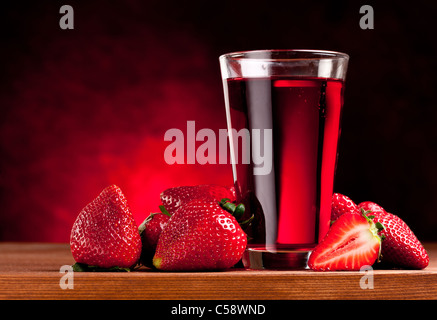 Glass with strawberry juice and berries. Isolated on a white background. - Stock Photo