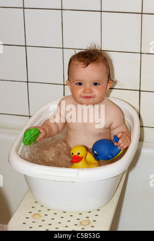Portrait of a little baby with toys enjoying a bath in bathtub - Stock Photo