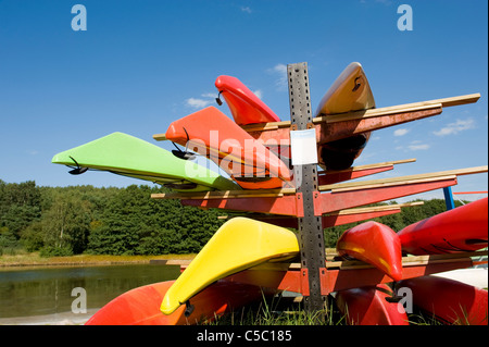 Close-up view of colorful kayaks on stand against blue sky - Stock Photo