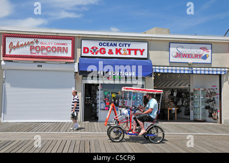 A couple pedal their surrey on the boardwalk at Ocean City, New Jersey - Stock Photo