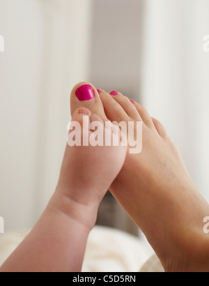 Close-up of a baby and woman's bare feet - Stock Photo
