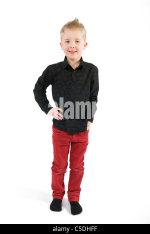 Full length portrait of a little boy standing against white background - Stock Photo