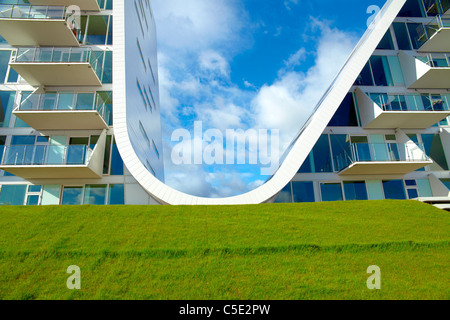 Cropped Bolgen wavy house against blue sky and clouds with grass in foreground at Vejle, Denmark - Stock Photo