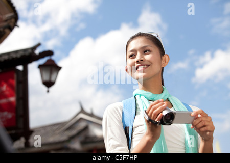 Young Woman Exploring Dali with Video Camera - Stock Photo