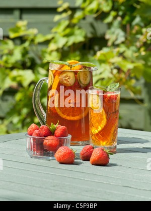 PIMMS AND STRAWBERRIES IN GARDEN IN SUMMER - Stock Photo