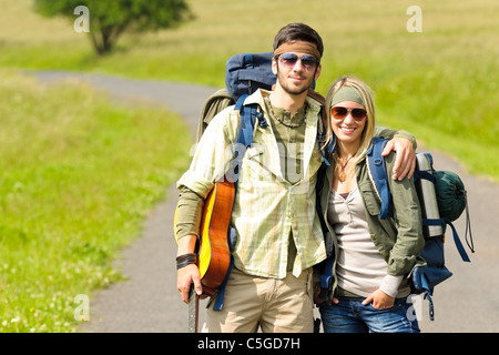 Hiking young couple backpack tramping on asphalt road sunny countryside - Stock Photo