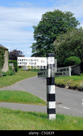 Old Black and White Road Sign in Hinton in the Hedges showing directions to Farthinghoe via a Gated Road - Stock Photo