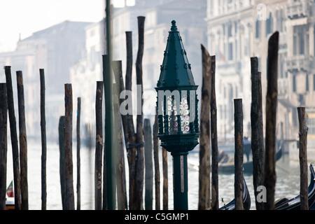 Gondola mooring posts and a decorative lamp, Venice, Italy - Stock Photo