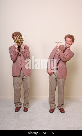 one man aiming a dart at his twin holding a target - Stock Photo