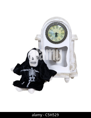 Time is running short with death incarnated leaning against a formal clock to measure time passing - path included - Stock Photo