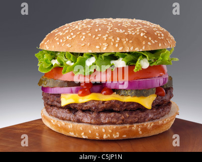 Cheeseburger with two beef patties lettuce red onion gherkin mayonnaise and tomato ketchup - Stock Photo