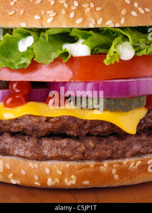 Cheeseburger with two beef patties lettuce red onion gherkin mayonnaise and tomato ketchup close up - Stock Photo