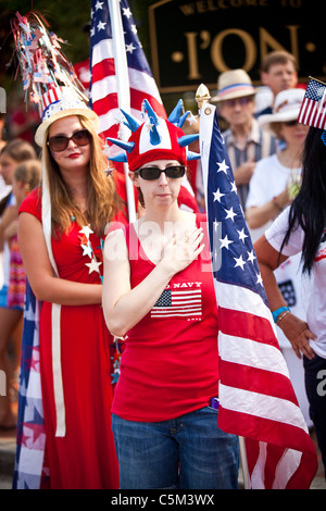 A woman dressed in patriotic costume stands for the flag in the I'On Community 4th of July parade. - Stockfoto