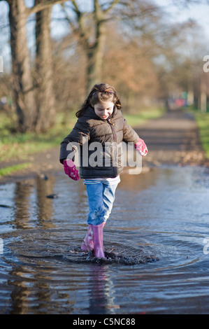 A young girl walking through a puddle, smiling - Stock Photo