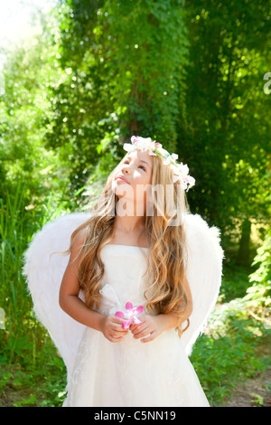Angel children girl in forest holds flower in hand looking sky with white wings - Stock Photo