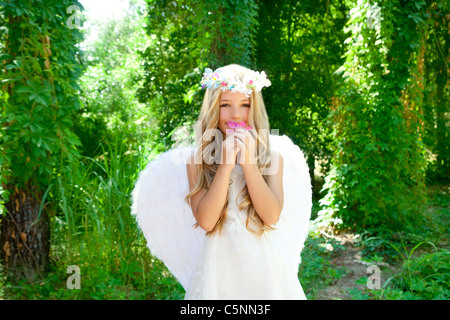 Angel children girl smelling pinks flower in forest with white wings and crown - Stock Photo