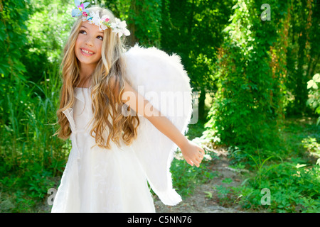 Angel children girl open arms in forest with white wings and flowers crown - Stock Photo