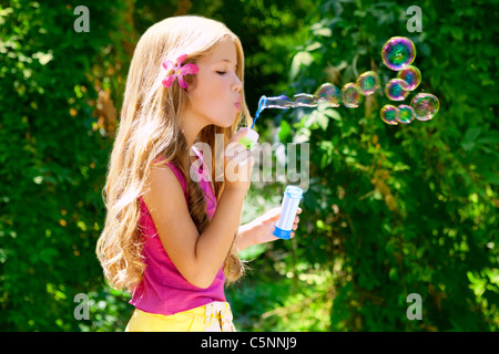 Children blowing soap bubbles in outdoor forest with fashion pink flower - Stock Photo