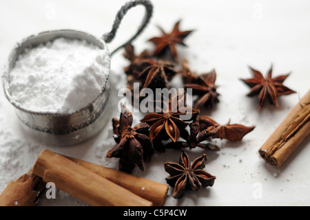 Baking ingredients: cinnamon sticks, star anise and icing sugar - Stock Photo