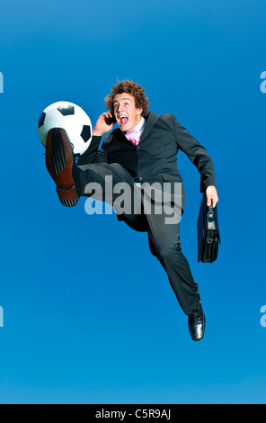 A happy businessman on a cell phone kicks ball. - Stock Photo