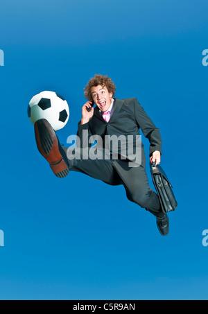 A businessman on a cell phone kicks ball. - Stock Photo