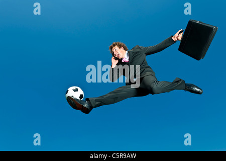A soccer playing businessman volleys ball whilst on cellphone. - Stock Photo