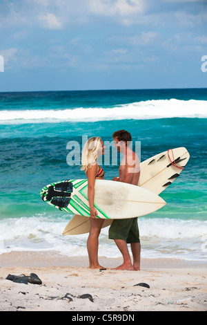 A couple of surfers in conversation on the beach. - Stock Photo