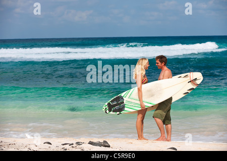 A surfing couple on beach. - Stock Photo