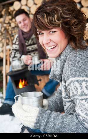 Austria, Salzburg Country, Flachau, Young man and woman making tea and sitting besides stove in winter - Stock Photo