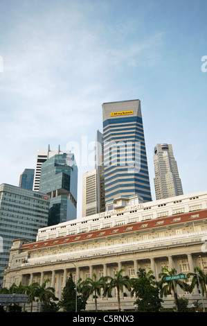 The Fullerton Hotel Singapore in front of the skyline of the financial district, five star luxury hotel in Singapore, - Stock Photo
