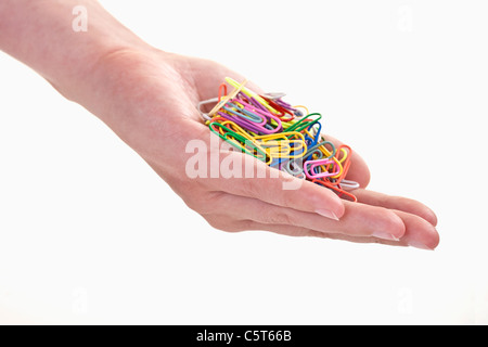 Close up of woman's hand holding paper clips against white background - Stock Photo