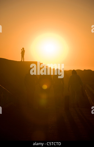 Tourists walk out to the breakwaters to watch the setting sun. Swakopmund, Namibia. - Stock Photo