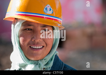 Woman laborer takes break from digging ditch, Dulan, Qinghai Province, China - Stock Photo