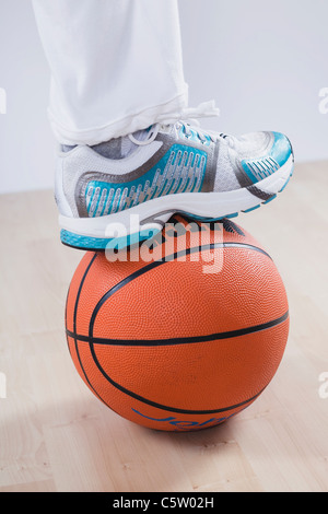 Close up of leg on basket ball against white background - Stock Photo