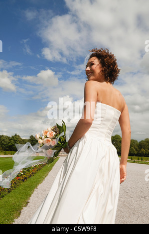 Germany, Bavaria, Bride in park with bunch of flowers, portrait - Stock Photo