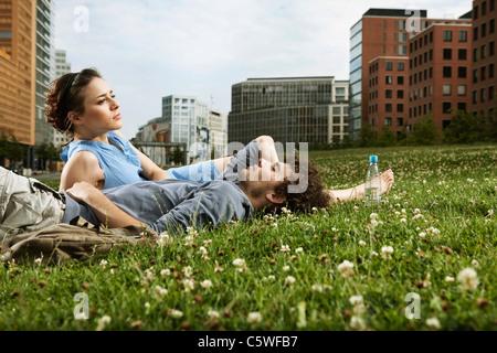 Germany, Berlin, Young couple lying in meadow, high rise buildings in background - Stock Photo