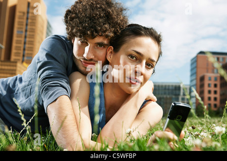 Germany, Berlin, Young couple lying in meadow, woman holding mobile phone, portrait, close-up - Stock Photo
