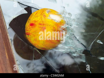 Close up of broken glass window by soccer ball - Stock Photo