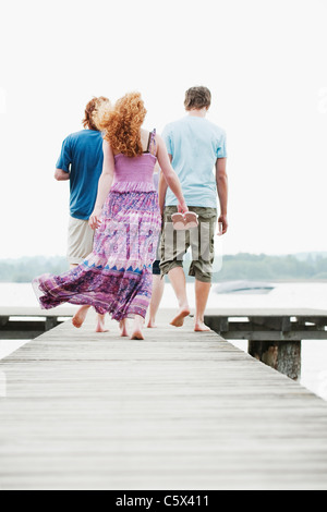 Germany, Bavaria, Ammersee, Four friends walking on jetty, rear view - Stock Photo