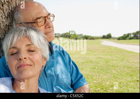 Spain, Mallorca, Senior couple sitting by tree, eyes closed, portrait, close-up - Stock Photo