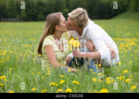 Austria, Young couple kissing in meadow, eyes closed, portrait - Stock Photo